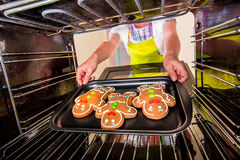 Baking Gingerbread man in the oven Stock Images