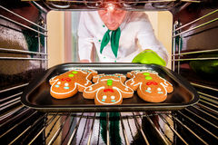 Baking Gingerbread man in the oven Royalty Free Stock Images