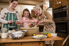 Baking With Grandma. Two sisters are baking cakes in the kitchen with their grandmother Royalty Free Stock Photography