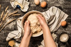 Baking - hands kneading the raw dough pastry in a bowl. Baking - cook`s hands kneading the raw dough pastry in a bowl. Wheat, butter, eggs, flour and sugar stock photography