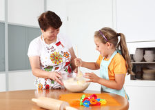 Baking and having fun. Grandmother and granddaughter baking and having fun together Stock Image