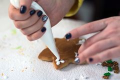 A female hand with dark nails squeezes a white glaze cream for decoration on a Christmas gingerbread in the form of a snowflake. B royalty free stock images