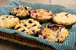 Baking homemade fresh fruit pies. Six homemade fresh fruit pies in a wicker tray made with strawberries raspberries blueberries blackberries Stock Photo