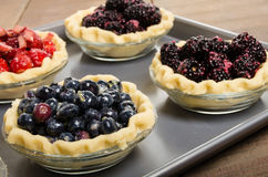 Baking homemade fresh fruit pies. Homemade fresh fruit pies on a tray made with strawberries blueberries blackberries Stock Images
