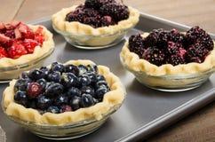 Baking homemade fresh fruit pies Stock Images