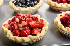 Baking homemade fresh fruit pies. Homemade fresh fruit pies on a tray made with strawberries raspberries blueberries Royalty Free Stock Photography