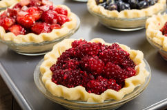 Baking homemade fresh fruit pies. Homemade fresh fruit pies on a tray made with strawberries raspberries blueberries Stock Image