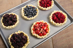 Baking homemade fresh fruit pies. Homemade fresh fruit pies on a tray made with strawberries raspberries blueberries blackberries Royalty Free Stock Photography