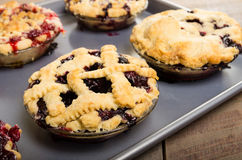 Baking homemade fresh fruit pies. Homemade fresh fruit pies on a tray made with strawberries raspberries blueberries blackberries Royalty Free Stock Images