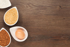 Baking Ingredient Border. All natural baking ingredients in petal shaped bowls. Pictured are Flour, sugar egg, and cocoa in pleasing warm colour tones stock image