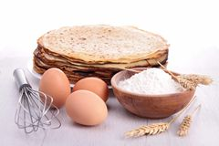 Baking ingredient and crepes. On wood Royalty Free Stock Image