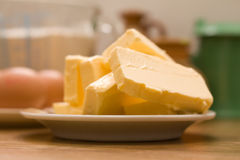 Baking ingredients. Margarine eggs and kitchen containers on the kitchen table Stock Photos