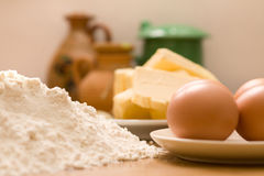 Baking ingredients. Margarine eggs flour and kitchen containers on the kitchen table Royalty Free Stock Images