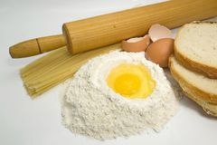 Baking ingredients. Egg in a pile of flour with pasta, bread and kitchen tools for cooking Stock Photos