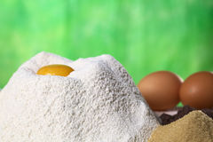 Baking Ingredients. Flour with egg yolk in the middle surrounded by brown sugar, chocolate chips and eggs (Selective Focus, Focus on the front of the flour pile Stock Image