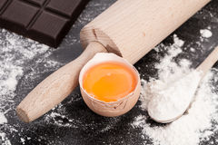 Baking ingredients. Baking background with flour, ingredients, rolling pin, making  dough and  pastry, homemade, preparation, recipe utensils,egg yolk next to Royalty Free Stock Photos