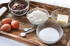 Baking ingredients for chocolate cake muffins or cookies. Lying ready on wooden kitchen tray. Mise en place of measured ingredients on white background Royalty Free Stock Image