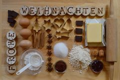 Baking ingredients for christmas cookies. With wooden pieces and the german words FROHE WEIHNACHTEN burned into them Stock Photo