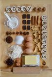 Baking ingredients for christmas cookies. With wooden pieces and the words MERRY CHRISTMAS burned into them Royalty Free Stock Images