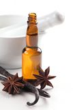 Baking ingredients. Close-up of vanilla beans, anise stars, mortar and baking flavor in a bottle stock photography