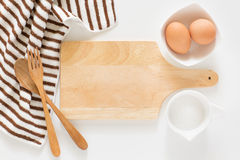 Baking ingredients for cooking and cutting board for recipes. Baking ingredients for cooking and wooden cutting board, spoon, egg and sugar for recipes on white Stock Photos