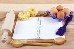 Baking ingredients for cooking and notebook for recipes. Baking ingredients for cooking and notebook for recipes on a wooden board Stock Image