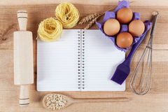 Baking ingredients for cooking and notebook for recipes. Baking ingredients for cooking and notebook for recipes on a wooden board Royalty Free Stock Photo