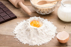 Baking ingredients with egg yolk. Flour with rollin pin on wooden background, making a cake, making homemade dough and pastry, rolling dough on pastry board Stock Images