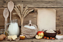 Baking ingredients. (eggs, flour, milk, butter, sunflower oil, cinnamon, hazelnuts, apples, oatmeal flakes) on wooden background with a blank sheet. Top view stock images