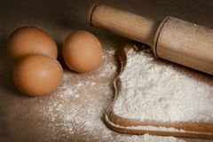 Baking ingredients eggs, flour and rolling pin on the table royalty free stock photos