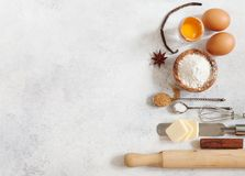 Baking ingredients flour, butter, sugar, salt, eggs. And spices on grey background, top view Stock Photos