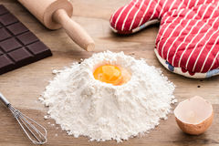 Baking ingredients with flour and egg yolk. Egg yolk with rolling pin and flour on black background, baking and making dough, homemade, baking ingredients on Royalty Free Stock Photo