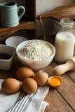 Baking ingredients flour, eggs, open yolk, milk, rolling pin, cupboard, raisins, rustic kitchen interior, utensils, dishware Royalty Free Stock Photo