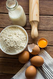 Baking ingredients flour, eggs, open yolk, milk, rolling pin, linen towel, rustic kitchen interior, utensils Royalty Free Stock Images