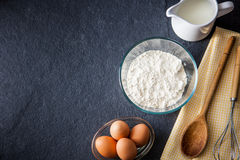 Baking ingredients - flour, milk, eggs with a whisk, Stock Image