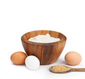Baking Ingredients. Flour Sugar and Eggs. Baking ingredients on a white background. Top of image, starting at halfway through eggs, is isolated stock photo