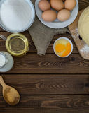 Baking ingredients for homemade pastry on dark rustic wood background. Vertical Royalty Free Stock Photo