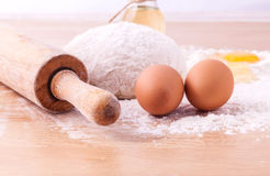 Baking ingredients including fresh eggs, flour and a rolling pin Stock Image