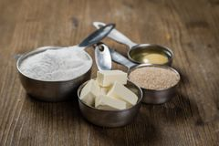 Baking ingredients in measuring cups. Rustic wood background stock images