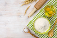 Baking ingredients, rolling pin and wheat ears on wooden table Royalty Free Stock Photo