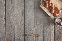 Baking ingredients on rustic wood background. Baking background. Cooking ingredients. Eggs carton and pastry brush on rustic wood. Top view with copy space stock image