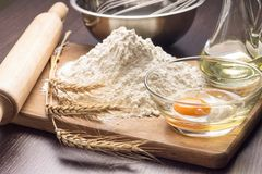 Baking ingredients with wheat ears on board Stock Photos