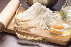 Baking ingredients with wheat ears on wood board Stock Photography