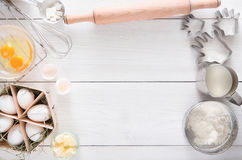 Baking ingredients on white rustic wood background, copy space. Baking background. Cooking ingredients for dough and pastry, eggs, flour and cookie cutter on stock photo