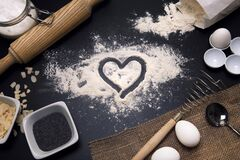 Baking love. Bakery background. Baking ingredients and kitchen utensils on the black background. Flour, almond nuts, eggs. Top