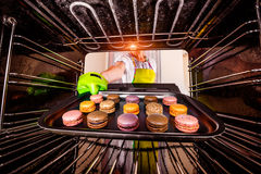 Baking macarons in the oven. Royalty Free Stock Images