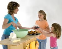 Baking Muffins. Mother and daughters baking blueberry muffins Stock Photo