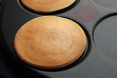 Baking pancakes on a crepe maker Royalty Free Stock Photography