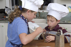 Baking a pie 2. Young boy and girl, brother and sister baking a pie for the holidays measuring ingredients Royalty Free Stock Images
