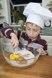 Baking a pie 3. Young boy baking a pie for the holidays mixing ingredients with a spoon Royalty Free Stock Images